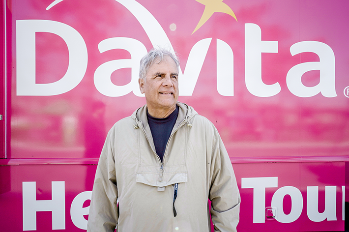 Man in tan jacket standing in front of the DaVita Health Tour bus
