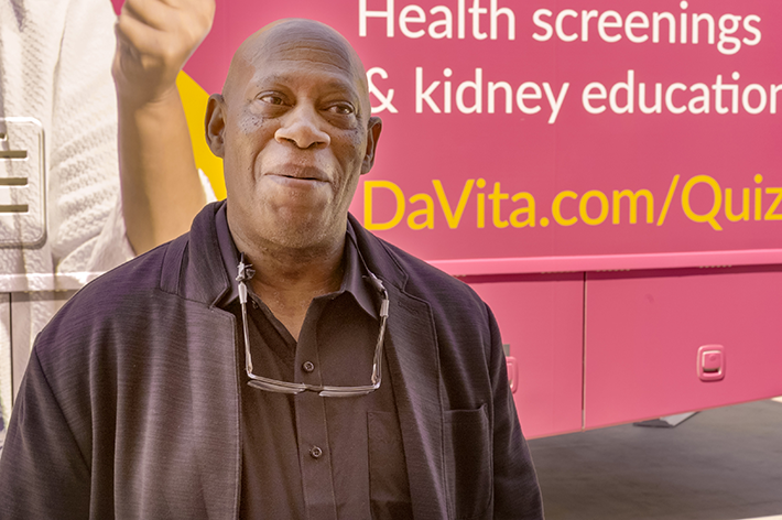 Man standing in front of the DaVita Health Tour bus