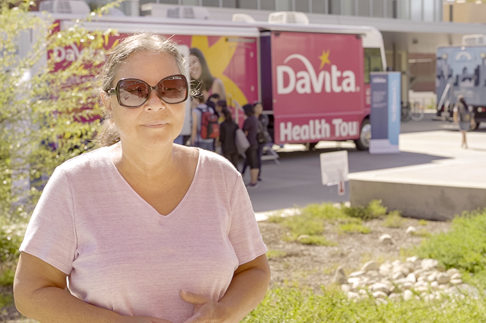 Woman in sunglasses standing in front of the DaVita Health Tour bus